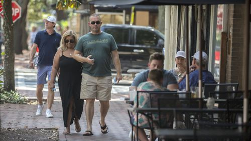 A couple walks past the Six Pence restaurant on Bull Street in the Historic Downtown Savannah. Savannah became the first major city in Georgia to require the use of face masks, setting up a potential showdown with Gov. Brian Kemp over whether local officials can take more sweeping steps than the state to contain the coronavirus. (AJC Photo/Stephen B. Morton)
